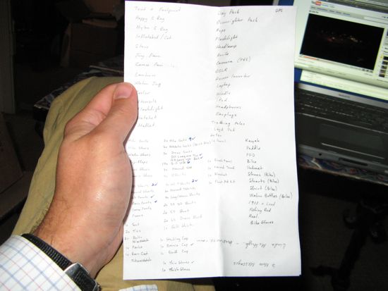 My hand, posing with my handwritten packing list.