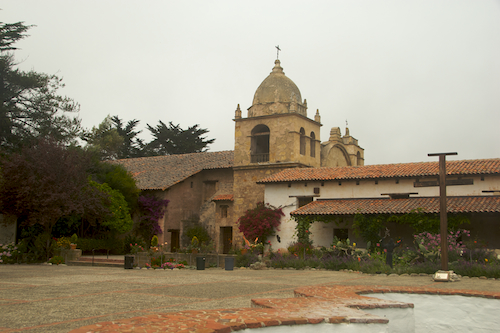 Carmel mission courtyard with tower, crosses, and fountain.